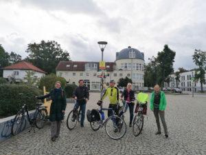 Gruppe mit Fahrrädern vor Bahnhof